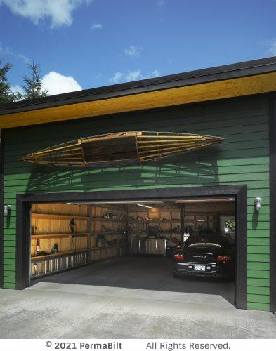 Pole barn garage with big garage door open and car and garage interior showing