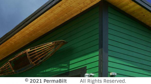 Corner of garage with enclosed soffits, green siding and black trim
