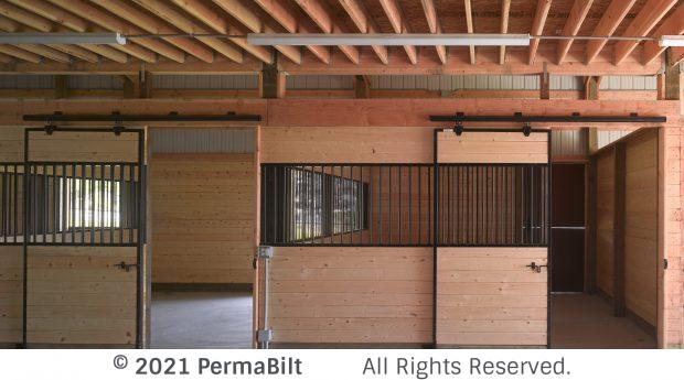 Interior of pole barn with 2 horse stalls with black grills and hardware
