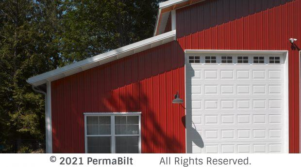 Red barn with white trim and one window and a garage door.