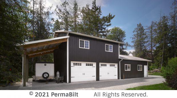 Two level garage with carriage style garage doors and a lean to off one side with a trailer parked in it.