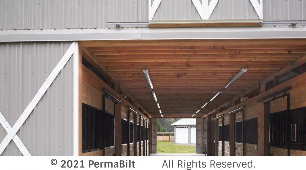 Horse pole barn with doors open and horse stalls inside